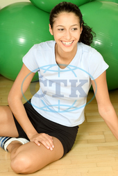 sporty young woman is sitting on the floor
