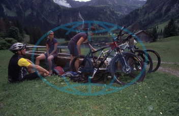 Mountain Bikers with Their Bikes have a Rest
