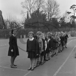 Schoolchildren line up in playground