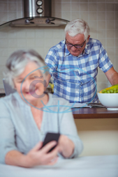 70s, Senior, Elderly, Woman, Female, Caucasian, Man, Male, Indoors, Standing, Kitchen, Counter, Leisure, Spare Time, Free Time, Activities, Reading, Using, Husband, Mobile Phone, Communication, Connection, Technology, Home,
