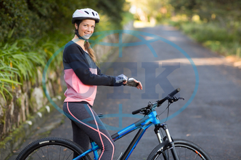 20s, Young Adult, Woman, Female, Caucasian, Countryside, Forest, Road, Cyclist, Athletic, Biker, Sportswear, Sportswoman, Sport Gloves, Bicycle Helmet, Standing, Smiling, Happy, Cheerful, Confidence, Wearing, Outdoorsy, He