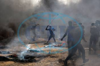 180514 GAZA May 14 2018 Palestinian protesters use slingshots to hurl stones at Israeli tr